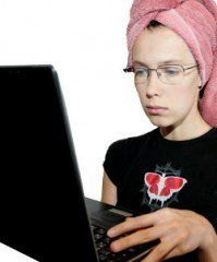 Young woman at her laptop with towel around her hair.