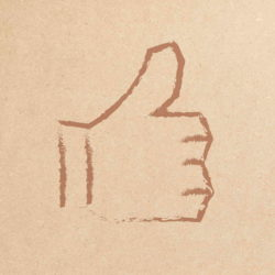 Woman holding board with thumbs up symbol on it