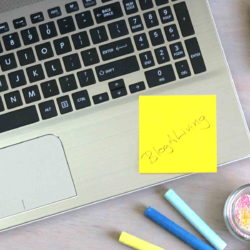 "Laptop with pens and a sticky note that says ""BlogALiving"""