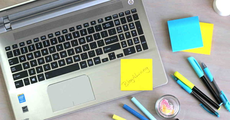 """Laptop with pens and a sticky note that says """"BlogALiving"""""""