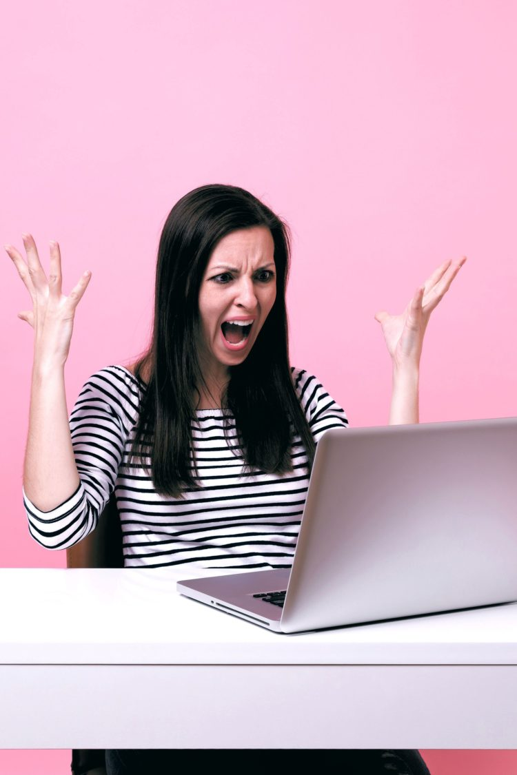 Angry woman throwing up her hands while looking at laptop