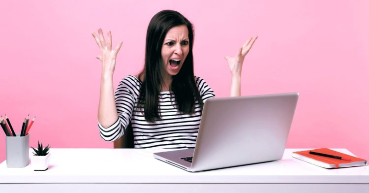Angry woman throws up hands while looking at laptop