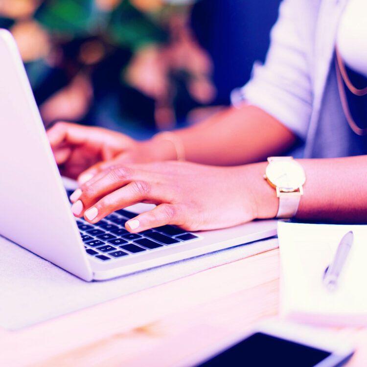 Woman writing blog post on laptop